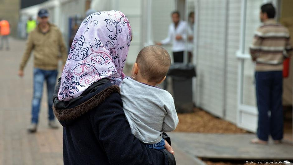 A woman carries her child in an initial reception facility in Bitburg, Germany | Photo: Picture-alliance/dpa/H.Tittel