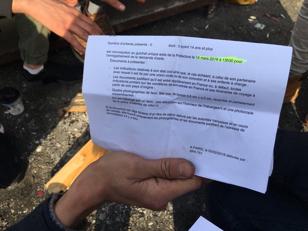Un demandeur d'asile montre le papier de rendez-vous pour la préfecture. Crédit : InfoMigrants