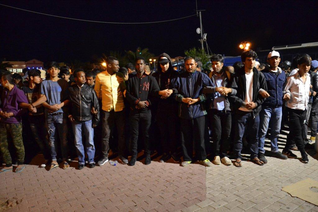 """Ansa / مهاجرون يحتجون في ميدان سابو بجزيرة ليسبوس، والشرطة تشكل حاجزا لحمايتهم من الجماعات اليمينية. المصدر: """"إي بي إيه""""/ أس تي أر."""