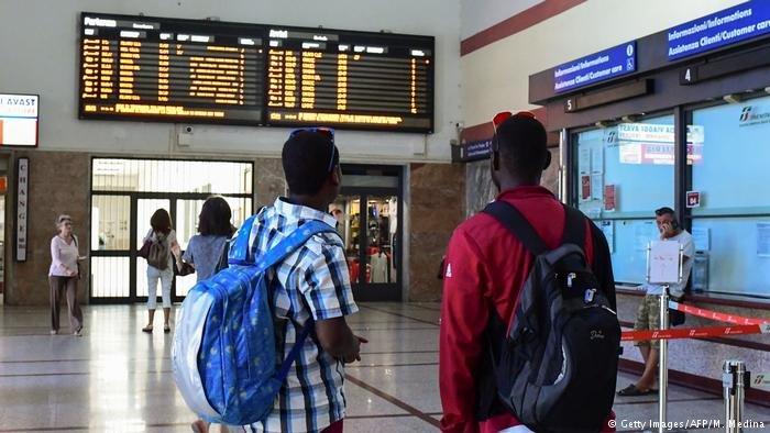 migrants study train timetables in the northern Italian city of Ventimiglia