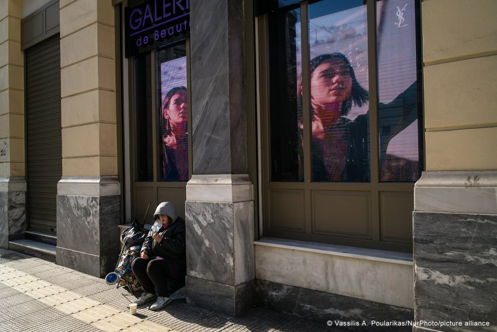 A homeless woman on Christmas day in front of a cosmetic shop in downtown Athens on December 25, 2020, Athens, Greece | Photo: Vassilis A. Poularikas/NurPhoto