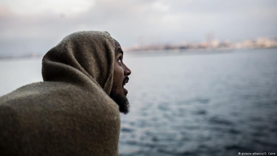 A migrant looks out as they approach port, from the deck of the Spanish NGO Proactiva Open Arms rescue vessel | Photo: Picture-alliance/O.Calvo