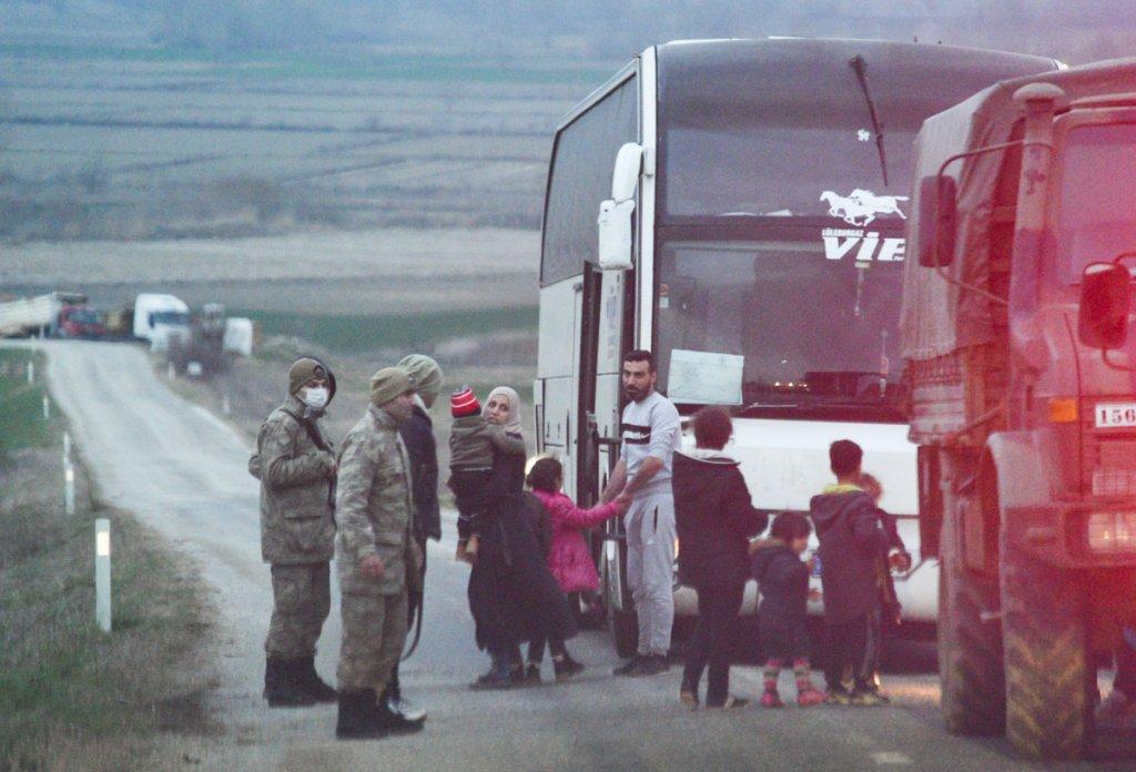 شاحنة عسكرية تنزل المهاجرين وتنقلهم إلى حافلة مدنية تقلهم إلى محطة الوقود بوجود عناصر من الجيش التركي. الصورة: مهدي شبيل