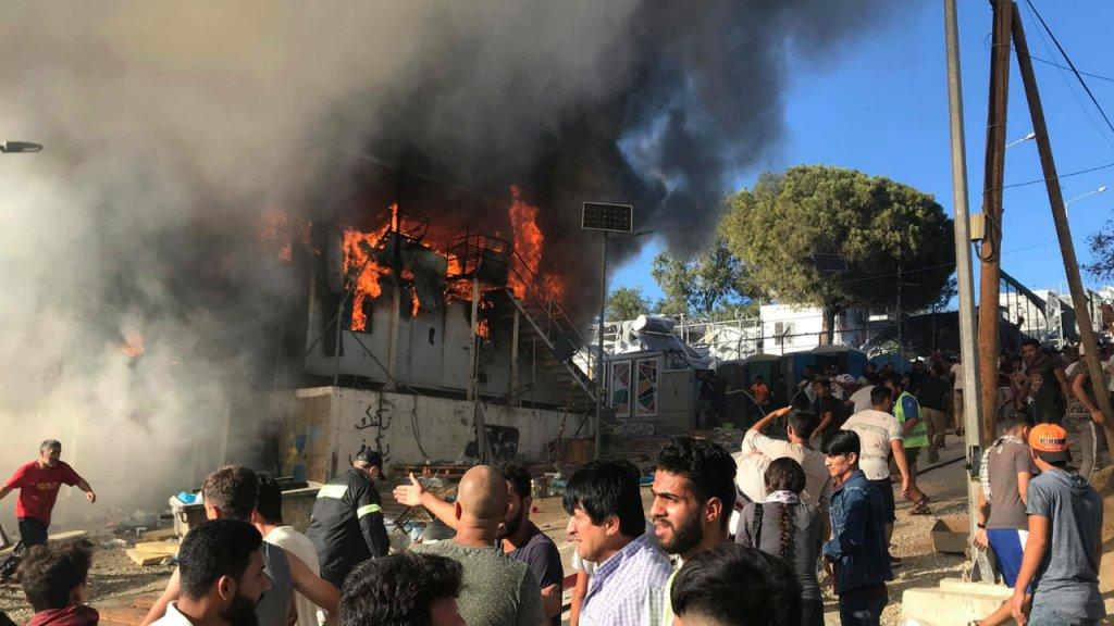 Des migrants se tiennent devant des conteneurs d'habitation en feu dans le camp de Moria sur l'île de Lesbos. Crédit : Reuters