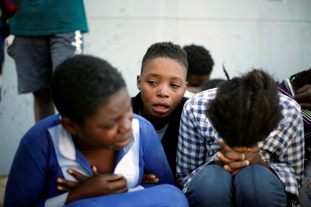 Deux migrantes et un enfant en pleurs en Libye. Crédits : Reuters (archive)