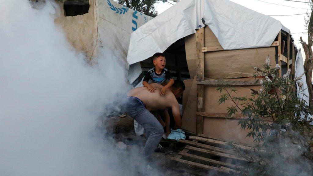 Un migrant porte un petit garon sur ses paules en tentant de fuir les tirs de gaz lacrymognes aprs lincendie du camp de Moria le 29 septembre Crdit  Reuters