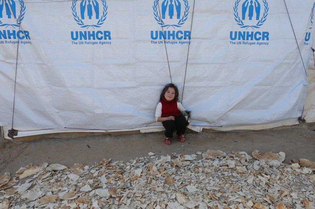 فتاة سورية صغيرة تجلس بجانب كومة خبز مجفف بمخيم للاجئين في عكار بلبنان   المصدر: رويترز/ محمد عزاقير