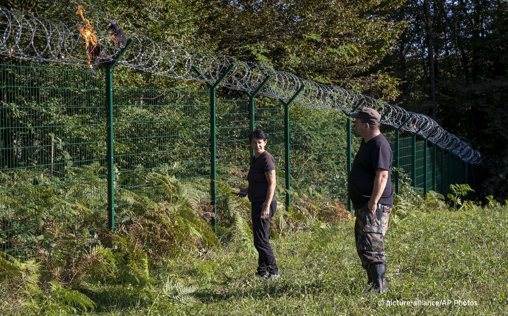 Blaz Zidar and his wife look at a burning jacket left by migrants on the razor-wire at the border fence between Croatia and Slovenia in the village of Radovica eastern Slovenia on September 4 2019  Photo APDarko Bandic