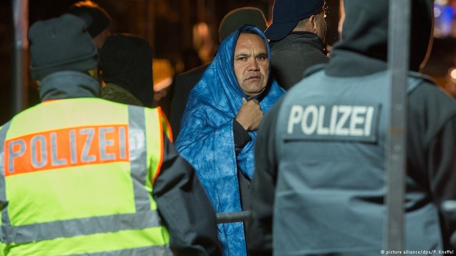 A man waits on the bridge between Braunau am Inn (Austria) and Simbach am Inn (Germany) in November, 2015