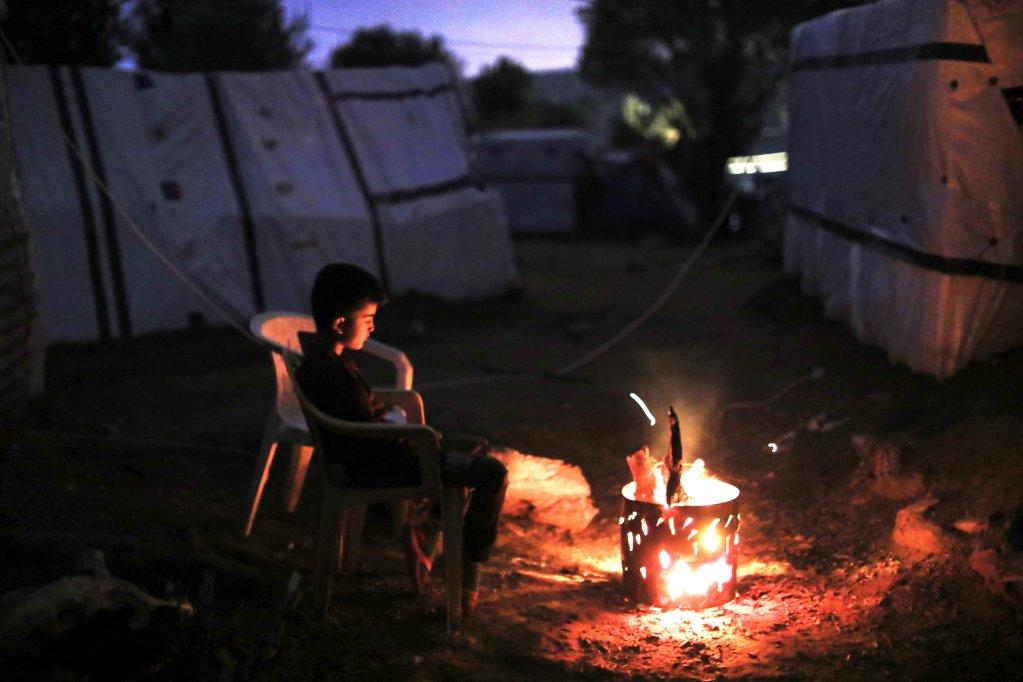 Un enfant se réchauffe près d'un feu dans un camp de fortune à Moria, sur l'île de Lesbos en novembre 2018. Crédit :  Giorgos Moutafis pour Oxfam