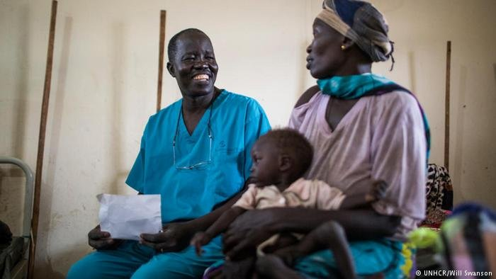 Dr Evan Atar Adaha sits with a South Sudanese refugee and her son at Maban hospital