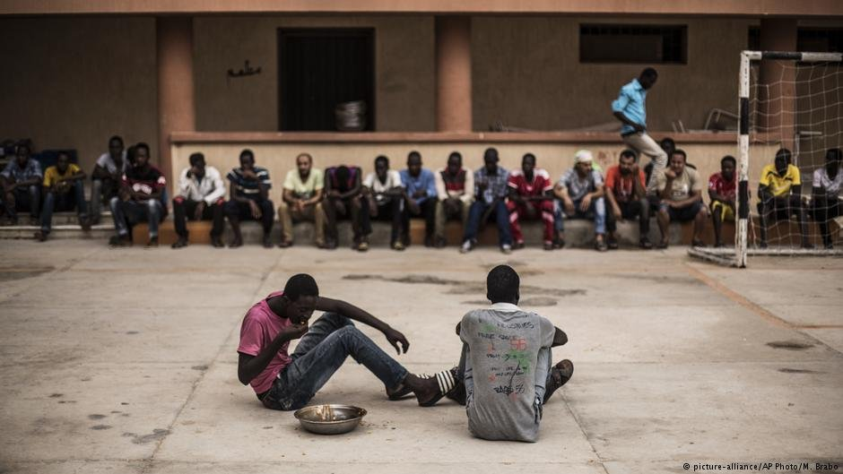 People sitting in a migrant detention center in Libya
