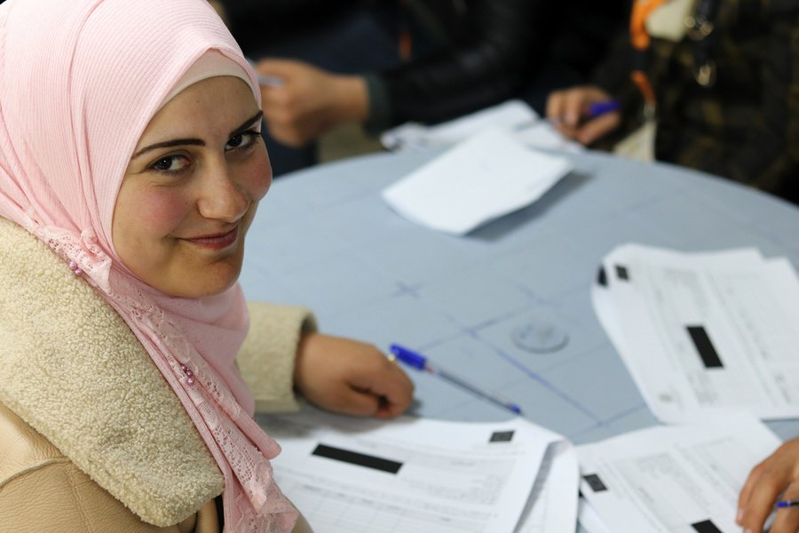 A woman smiles after completing her form in Amman in March 2019 | Photo: IOM / Abby Dwommoh