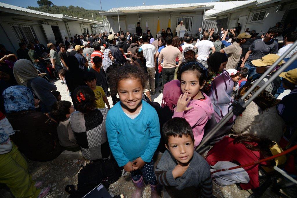 """أطفال ينظرون إلى المصور خلال إلقاء البابا فرنسيس كلمة في مخيم موريا بجزيرة ليسبوس في نيسان/أبريل الماضي، في رحلة استهدفت دعم اللاجئين وجذب الأنظار إلى أزمة الهجرة. المصدر: """"إي بي إيه""""/ فيليبو مونتيفورتي"""