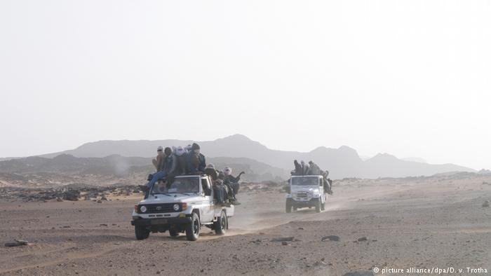 Migrants on a truck going across the desert
