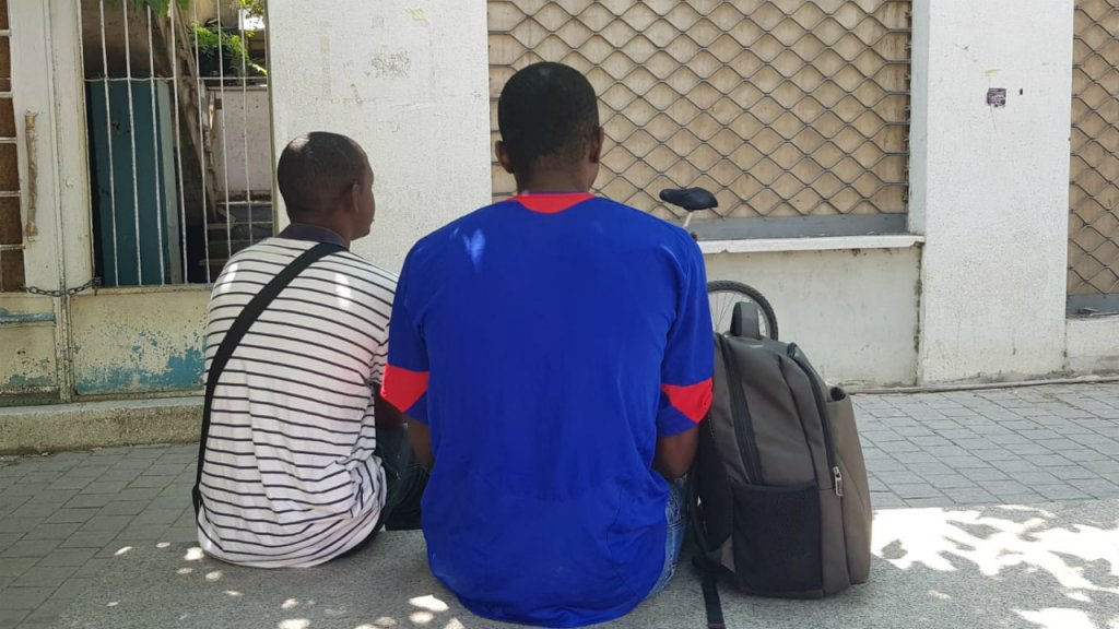 Thierry centre et son ami Ousmane sont assis devant le centre pour migrants de Caritas  Nicosie Ils y viennent pour sociabiliser et recevoir du soutien dans leur procdure de demande dasile Crdit  Anne-Diandra Louarn  InfoMigrants