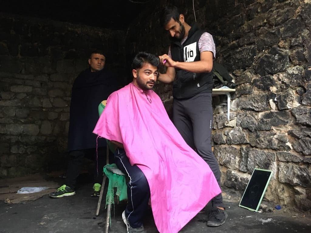 """مصطفى يقوم بتسريح شعر المهاجرين في """"بيت المشردين"""" في بيهاتش"""