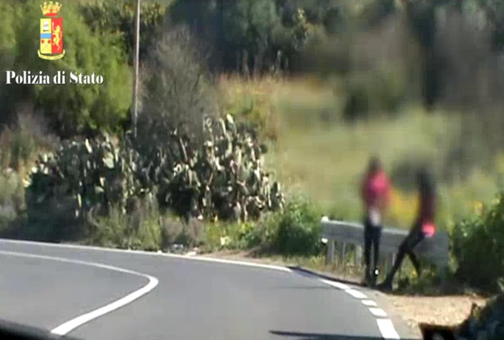 ansa / فتاتان أفريقيتان تعملان في الدعارة تنتظران الزبائن في أحد الطرق في صقلية المصدر: الشرطة الإيطالية/ أرشيف.