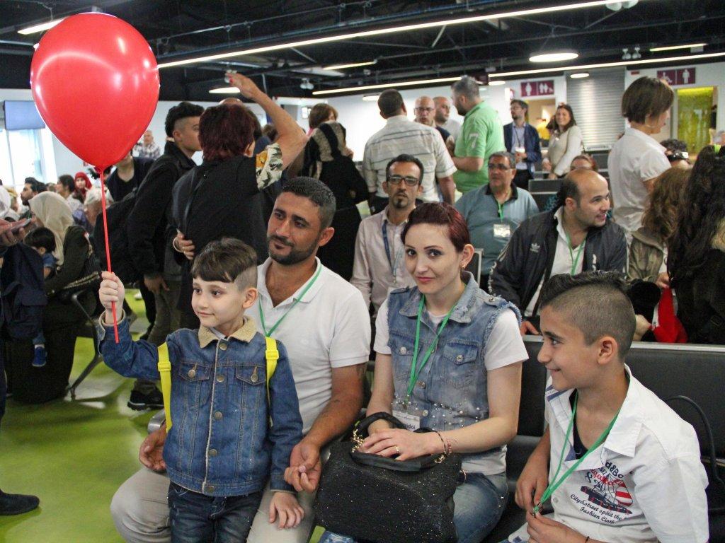 """ansa / مهاجرون سوريون وأسرهم يصلون إلى مطار فيوميتشينو في روما بفضل الممر الإنساني، الذي تدعمه مؤسسة """"سانت إيجيديو"""" واتحاد """"الكنائس الإنجيلية في إيطاليا"""" و""""تافولا فالديس"""". المصدر: سانت إيجيديو/ أنسا."""