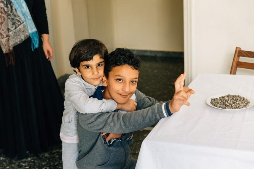 This photo shows Amir, the 11-year old from Afghanistan who will be the flagbearer and his younger brother Credit: LIFO.gr)