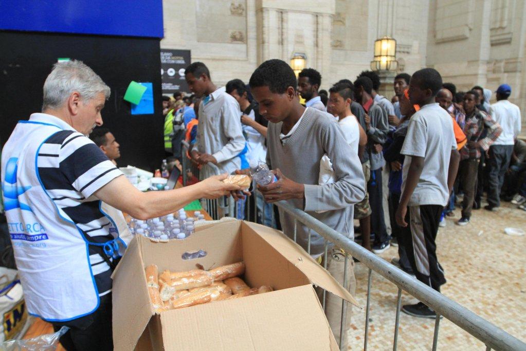 ansa / مهاجرون يتزاحمون للحصول على الطعام في محطة القطار الرئيسية في ميلانو. المصدر: أنسا.