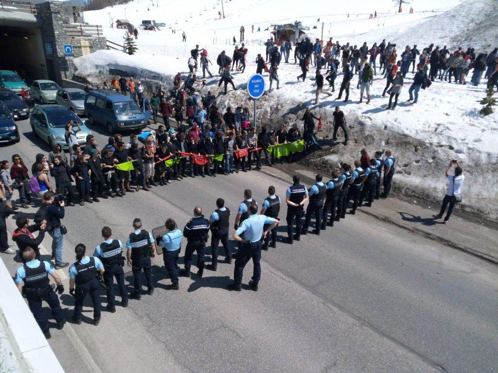 """Des militants lors d'une """"traversée solidaire"""" font face à un cordon policier au Montgenèvre dimanche 22 avril. Crédit : Luca Perino."""