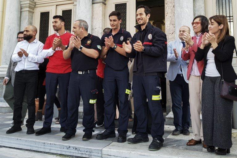 Anthi PAZIANOU / AFP |Les trois pompiers espagnols de l'ONG Proem-Aid, lundi 7 mai devant la cour de justice de Lesbos, après l'annonce de leur acquittement par la justice grecque.