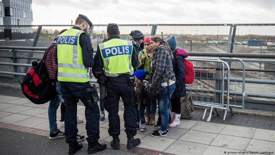 Swedish police talk to migrants on the bridge between Sweden and Denmark