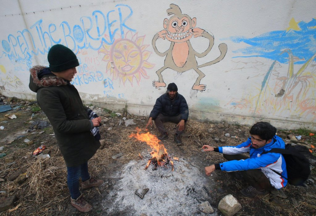 migrants try to get warm from an open fire as they take refuge in an abandoned warehouse near the border with Croatia in Adasevac, Serbia. Archive EPA/KOCA SULEJMANOVIC