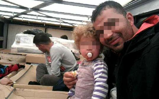 Kajin, caché dans un camion, tient un enfant en bas âge dans ses bras, lors d'une tentative de passage en Angleterre. Crédit : InfoMigrants