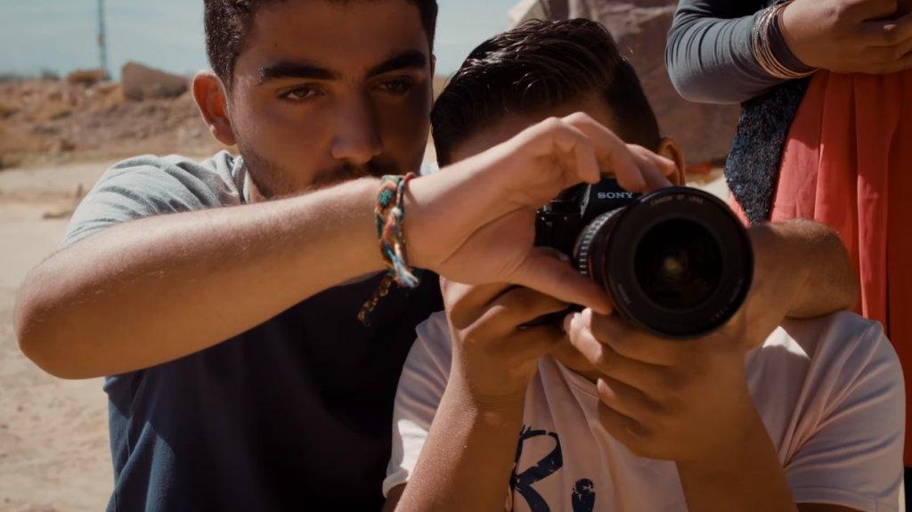 Mohamad Al Jounde enseigne les rudiments de la photo à un jeune réfugié. Crédits : KidsRights Foundation