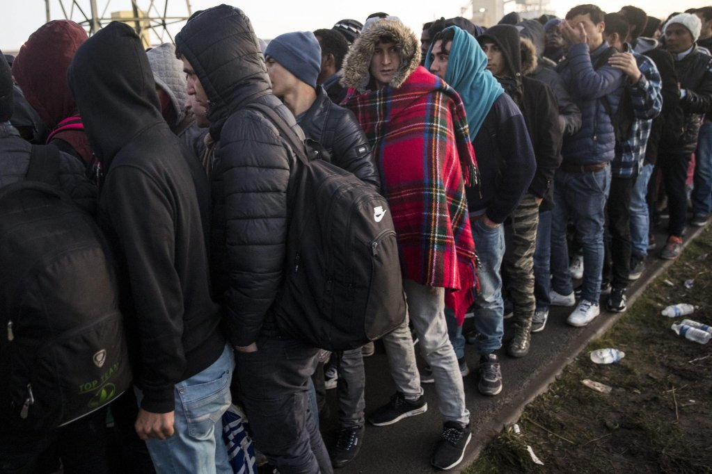 Migrants waiting in line near a process center to be transferred in a center near Paris (Credit: epa)