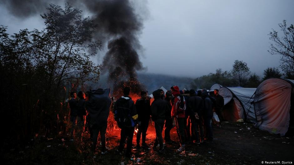 A group of people huddles in front of a fire thick black smoke billowing  Photo ReutersM Djurica