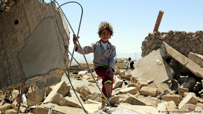 A Yemini child stands over the rubble of a destroyed house