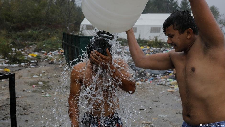 A man tipping water from canister over another man   Photo ReutersM Djurica