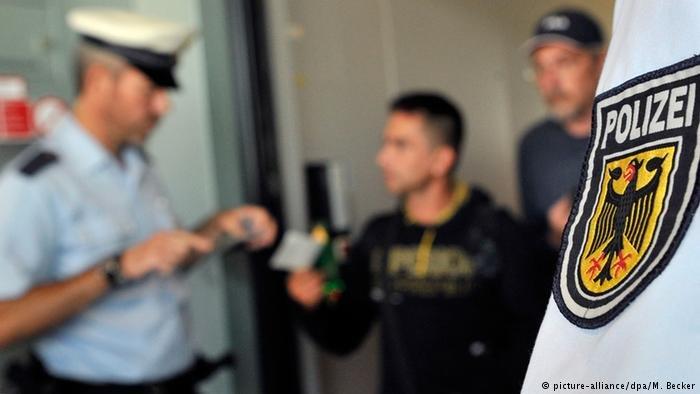 الشرطة الألمانية تقوم بالتحقق من وثائق سفر أحد المسافرين