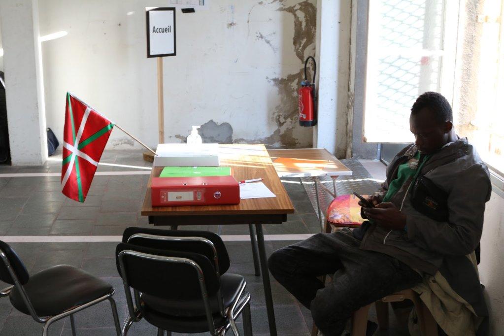 Un jeune migrant se repose prs du bureau daccueil du centre dhbergement Pausa de Bayonne o flotte le drapeau basque Crdit  InfoMigrants