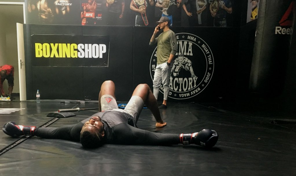 Francis Ngannou collapses on the floor after his training session Credit  InfoMigrants