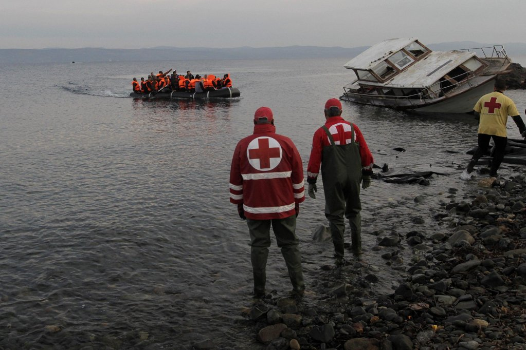 An overloaded rubber dinghy arrives on the Greek island of Lesbos  as Red Cross staff wait to assist them | Archive photo EPA