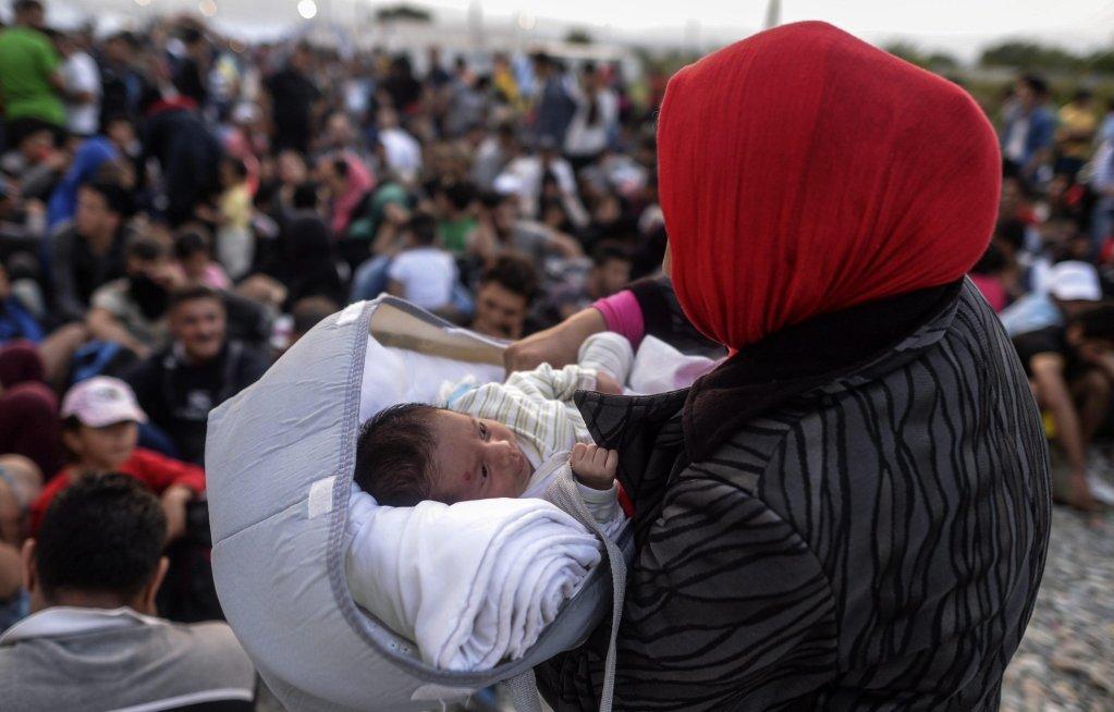 "ANSA / مهاجرة وطفلها في مركز تسجيل، حيث تنتظر القطار المتوجه إلى الحدود الصربية، بالقرب من مدينة ""جيفيجليا"" في شمال مقدونيا. المصدر: إي بي إيه/ جورجي ليكوفسكي."