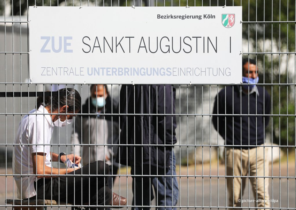"""People wearing protective masks while standing on the premises of the """"central accommodation facility"""" ZUE Sankt Augustin I on May 18, 2020 