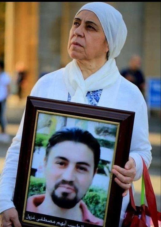 اختفت آثار أيهم بعد اعتقاله عام 2012، لتظهر صوره لاحقا من بين ضحايا التعذيب. تظهر في الصورة مديرة الرابطة مريم الحلاق وهي تحمل صورة ابنها.