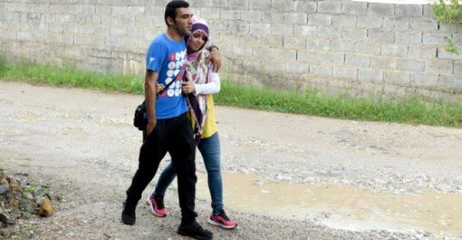 أ ف ب |اللاجئان السوريان أسمر ألوس وزوجته بيريفيان وهما في طريقهما إلى مركز للمهاجرين في تيرانا، 19 يونيو/حزيران 2018