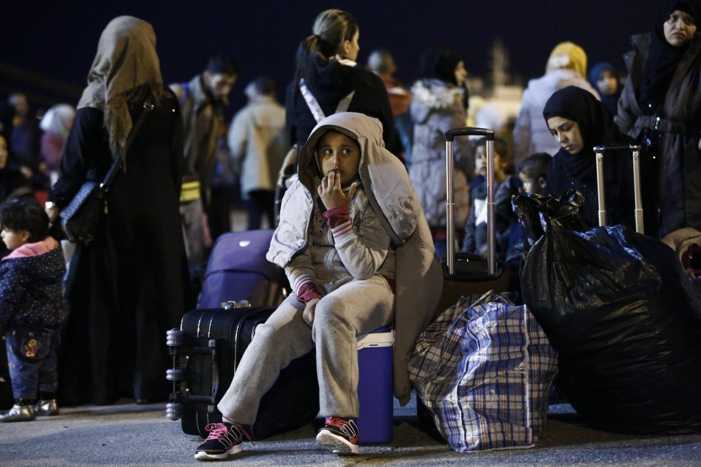 This picture shows refugees holding their belongings wait to enter a bus after their arrival with the 'Blue Star 2' passenger ship from the island of Samos, at the port of Piraeus, near Athens, Greece. Credit: EPA/ Yannis Kolesidis