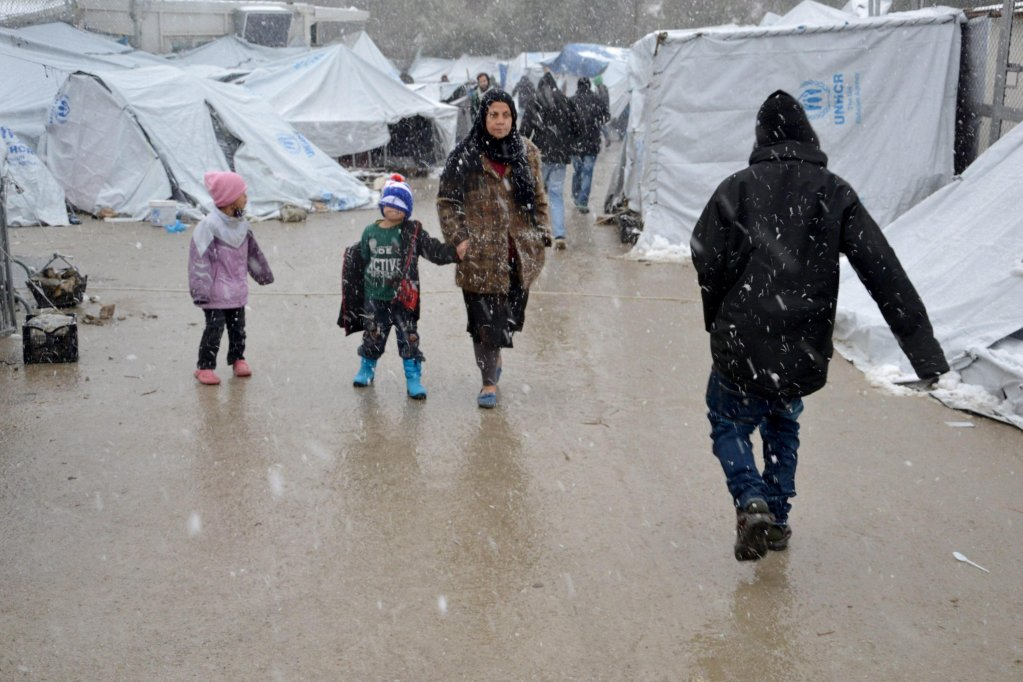 Refugees walk in the snow at the Moria refugee camp on Lesvos Island, Greece