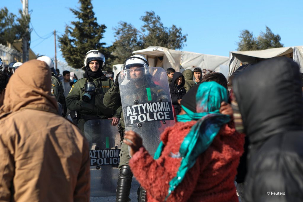 Migrants stand in front riot police officers during a protest outside the Moria camp on the Greek island of Lesbos after the fatal stabbing of a migrant on January 17, 2020 | Photo: REUTERS/Elias Marcou