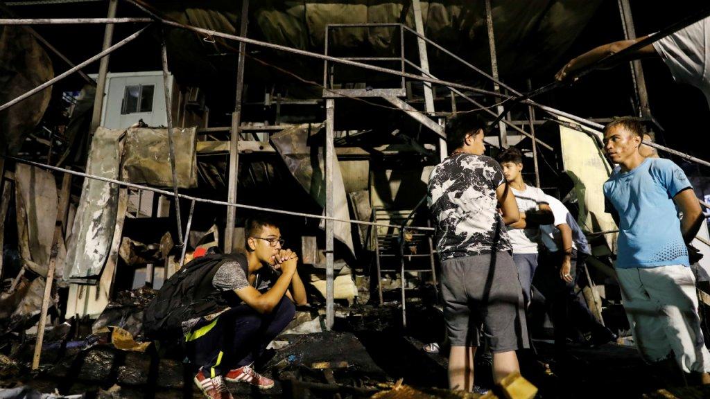 Des migrants se tiennent devant les conteneurs brûlés lors d'un incendie à Moria, le 29 septembre 2019. Crédit : Reuters