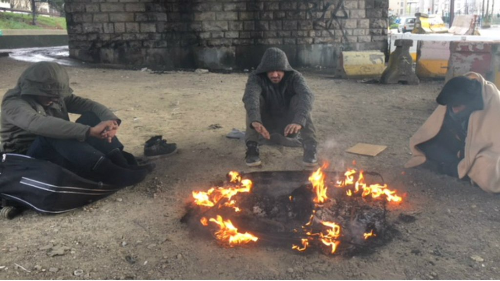 Charlotte Wilkins, FRANCE 24 | Three friends from Afghanistan gather around a fire in Paris's Porte de la Chapelle on 1 January 2018