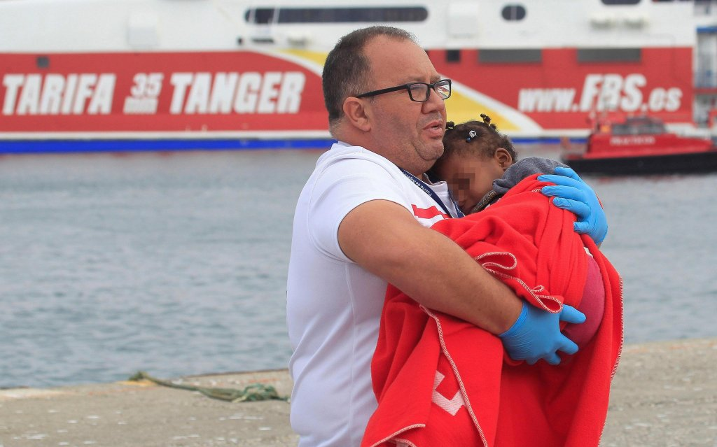 A member of the Spanish Red Cross at the port of Tarifa (southern Spain) carries a baby, one of 245 migrants that were rescued at sea, 13 July 2018. Spanish Maritime Rescue services rescued a total of 245 people who were trying to reach Spain traveling on ten small boats. EPA/A.CARRASCO RAGEL