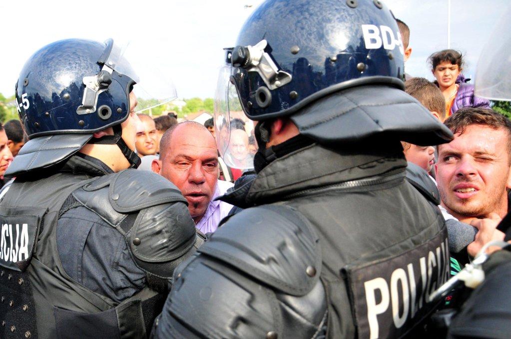 Slovenian police hold people back at the border crossing between Rigonce in Slovenia and Harmica in Croatia. | Photo: EPA/IGOR KUPLJENIK